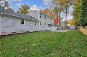 Rear yard of a custom home in the fall by Premier Designs Custom Homes LLC.