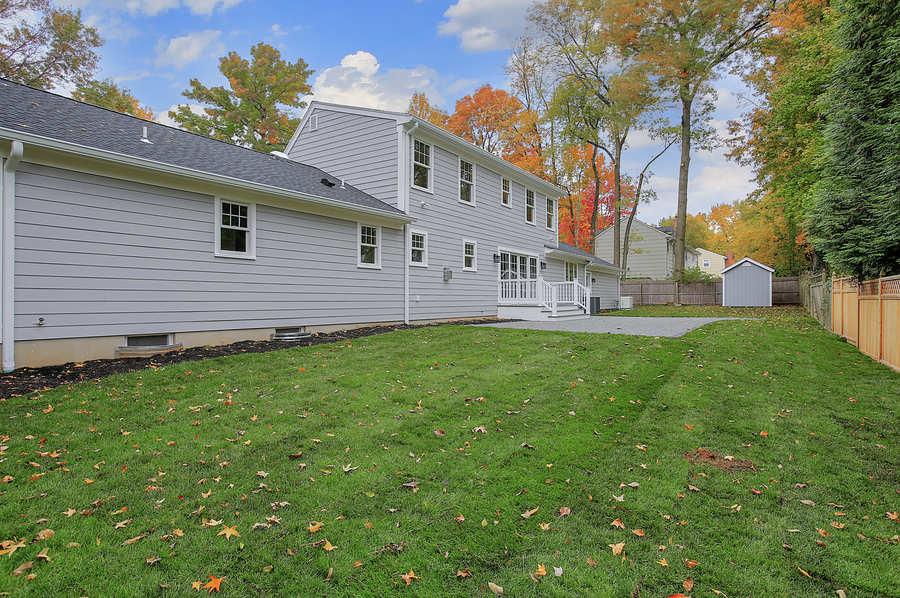 The rear yard of a custom home in the fall by Premier Designs Custom Homes LLC.